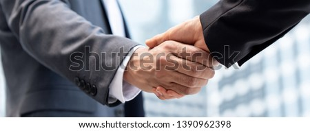 Businessmen making handshake in the city for merger and acquisition concept, panoramic banner #1390962398