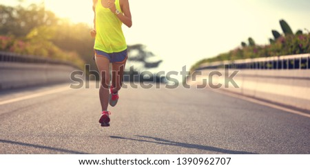 young fitness asian woman runner running on city road #1390962707