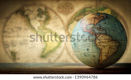 Old globe on vintage map background. Selective focus. Travel, stories and education background.  #1390964786