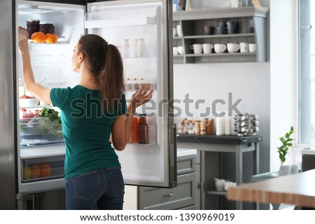 Woman taking food out of fridge at home #1390969019