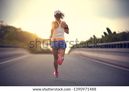 young fitness asian woman runner running on city road #1390971488