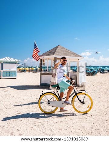 young men in swim short on the beach Miami, colorful Miami beach #1391015069