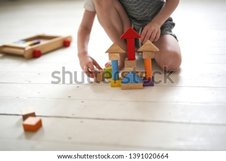A lonely boy plays wooden constructor on the floor in a light real interior of the house. Concept childhood, dreams of home. Selective focus and toning #1391020664