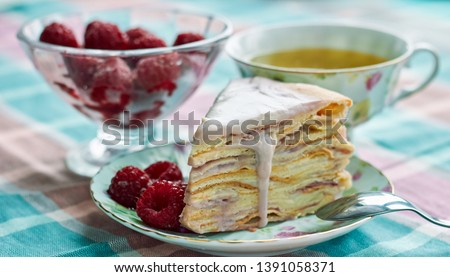 Homemade layer cake with raspberry vanilla custard dripping decorated with berry, table setting: cups of tea, spoons, dessert and ice-cream bowl with frozen fruit, close up, copy space Royalty-Free Stock Photo #1391058371