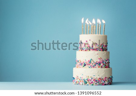 Birthday cake with three tiers and colorful sprinkles #1391096552