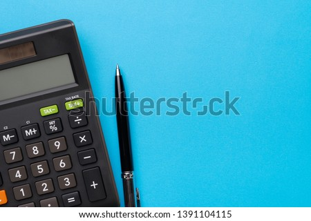 Financial activity, accounting, tax calculation or saving and investment, black calculator with pen on solid blue background with copy space. #1391104115