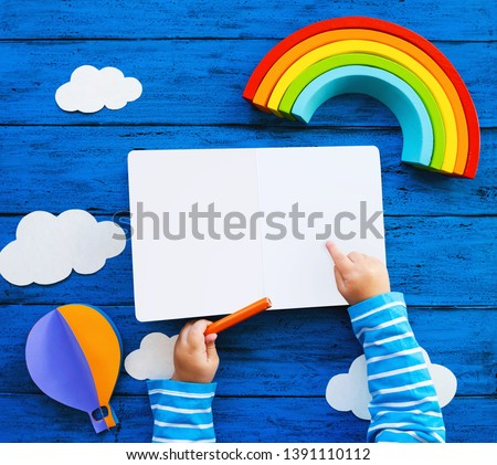 Creative children's waldorf or montessori school concept. Paper crafts, colored pencils, wood rainbow and blank book with child hands on blue table. Kids art class, kindergarten, preschool background #1391110112