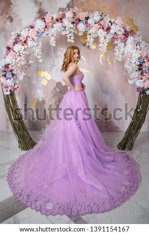 Elegant bride in a long lush lilac dress with a train under the arch of flowers. #1391154167