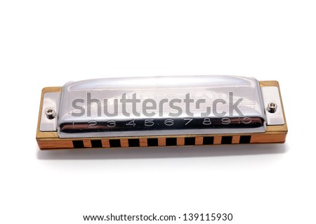 Harmonica, also French harp, blues harp, and mouth organ, isolated on white background. Is a free reed wind instrument used worldwide in blues, American folk  music, jazz, country, and rock and roll. Royalty-Free Stock Photo #139115930