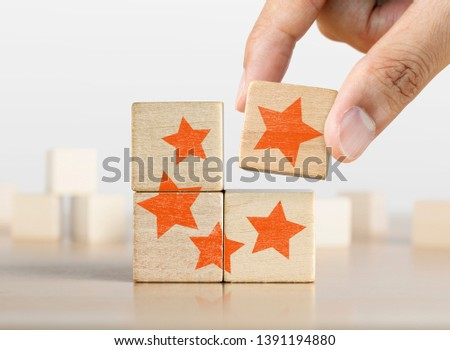 Hand putting the last piece of wooden blocks with the five star symbol. The best rating, the best ranking, the best service, goal, success concept. #1391194880