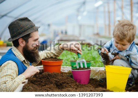 nature and care. father and son care nature. nature and care concept. family care about nature in greenhouse. everything for your gardening needs #1391207393