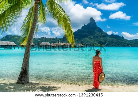Bora Bora luxury hotel vacation tourist woman relaxing by ocean beach with view of Mt Otemanu in Tahiti, French Polynesia. High End resort with overwater bungalows villas. #1391230415