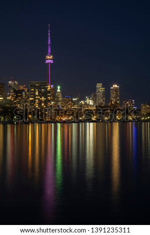 Urban landscape - Toronto City skyline at night, clear dark sky, colorful light reflection in the calm water surface of lake Ontario. Long exposure. Big city nightlife concept. #1391235311