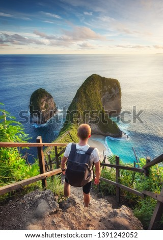 Traveler look at the ocean and rocks. Travel and active life concept. Adventure and travel on Bali, Indonesia. Travel - image #1391242052