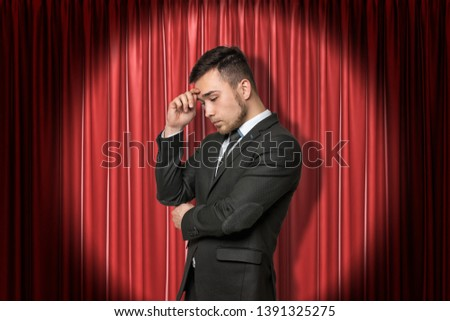 Young businessman thinking on red stage curtains background. Digital art. Brainstorm ideas. Business and commerce. #1391325275