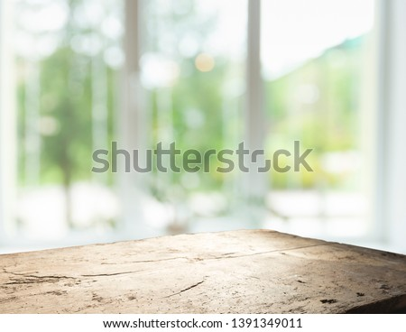 Wood table top on blur of window glass and abstract green from garden with city view in the morning background. For montage product display #1391349011