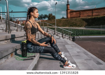 Beautiful girl athlete in tattoos, summer city, resting after fitness workout. Sportswear leggings top. Shaker with water protein skipping, rope smartphone headphones. Free space. Listening music. #1391351828