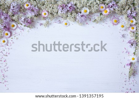 Spring background with blooming spirea branches, lilac flowers, daisies and petals for congratulations, text