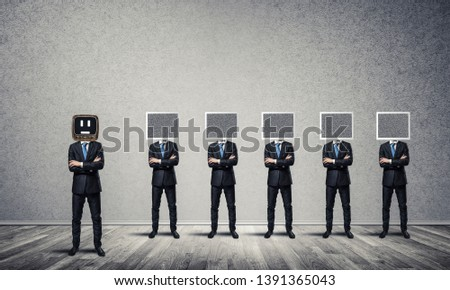 Businessmen in suits with monitors instead of their heads keeping arms crossed while standing in a row and one at the head with old TV in empty room against gray wall on background. #1391365043