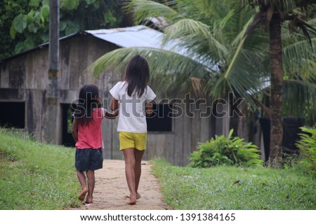 Leticia, Colombia - February, 2019: The people in the Amazon, two sisters are walking in an indigenous village in the Colombian Amazon.
