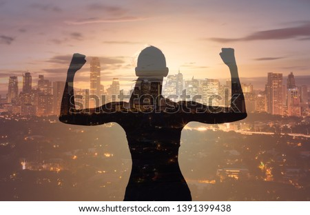 Victory and success! Silhouette strong confident woman flexing against a city skyline background. Double exposure #1391399438