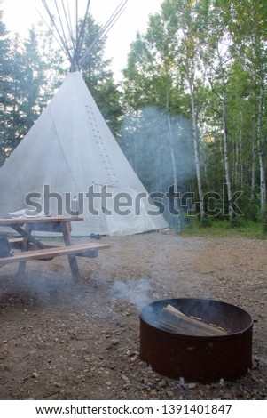 Picture of a tipi with fire pit and picnic table on a campground in Alberta, Canada.