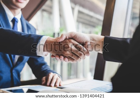 Finishing up a meeting, handshake of two happy business people after contract agreement to become a partner, collaborative teamwork. #1391404421
