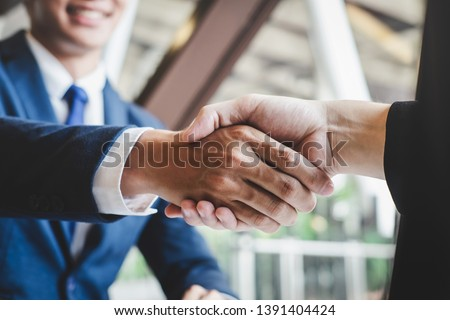 Finishing up a meeting, handshake of two happy business people after contract agreement to become a partner, collaborative teamwork. #1391404424