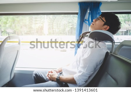 Young Asian man traveler sitting on a bus and sleeping with pillow, transport, tourism and road trip concept. #1391413601