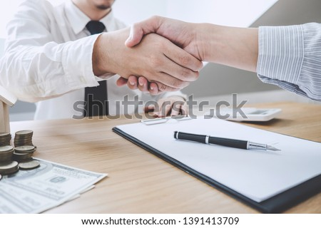 Real estate broker agent and customer shaking hands after signing contract documents for ownership realty purchase, Concept mortgage loan approval. #1391413709