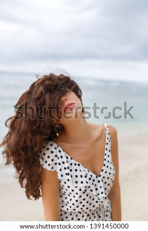 A beautiful girl with wavy brown hair, dressed in a polka-dot dress, stands on the seashore, and with her eyes half-closed, she throws her hair back #1391450000