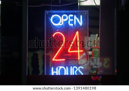 A Spring 2019 night photo of a 24 hour Open Hours sign in a store on Rideau St. downtown Ottawa, ON, CAN.
