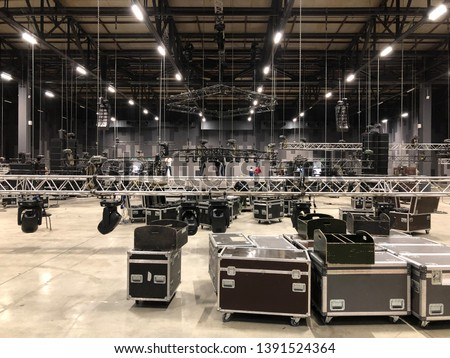 Installation of professional sound, light, video and stage equipment for a concert. Stage lighting equipment is clamped on a truss for lifting. Flight cases with cables. #1391524364