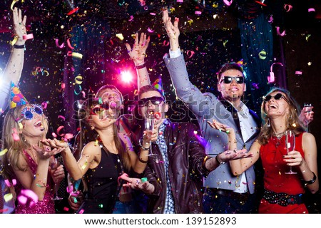 Cheerful young people showered with confetti on a club party. Royalty-Free Stock Photo #139152893