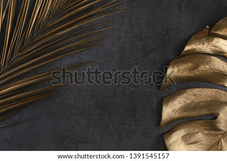 Closeup of golden palm and monstera leaves on abstract dark grey textured background. Tropical conceptual elegant trendy summer background. Flat lay. Copy space. Royalty-Free Stock Photo #1391545157