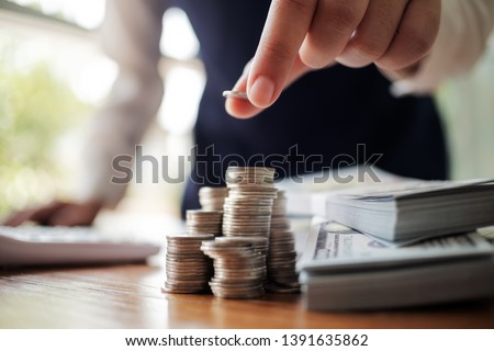 Business women put coin stack money and many bank note in office, Save money for future and Retirement.  Royalty-Free Stock Photo #1391635862