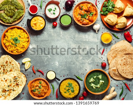 Indian cuisine dishes: tikka masala, dal, paneer, samosa, chapati, chutney, spices. Indian food on gray background. Assortment indian meal with copy space for text in center. Top view or flat lay. #1391659769