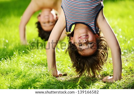 Portraits of happy kids playing upside down outdoors in summer park Royalty-Free Stock Photo #139166582
