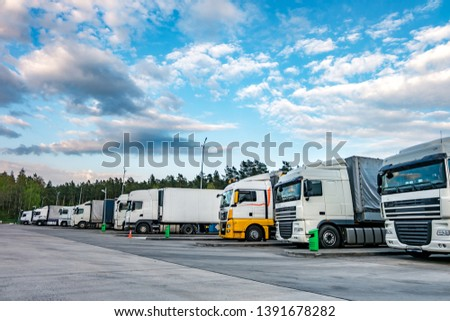 Trucks in a row with containers in the parking lot near forest , Logistic and Transport concept #1391678282