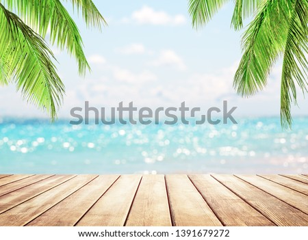 Wooden table top on blue sea and white sand beach background. Coconut palm trees against blue sky and beautiful beach in Punta Cana, Dominican Republic. Vacation holidays background wallpaper.  #1391679272