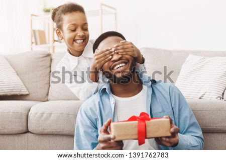 Father's day. Happy daughter congratulating dad and giving present at home #1391762783