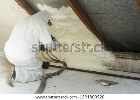 spray polyurethane foam for roof - technician spraying foam insulation using plural component gun for polyurethane foam, inside #1391800520