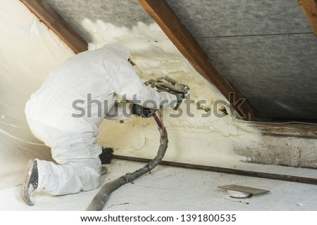 spray polyurethane foam for roof - technician spraying foam insulation using plural component gun for polyurethane foam, inside #1391800535