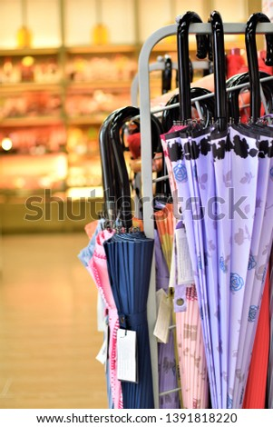 Umbrellas of different colors and designs on display at a convenient store #1391818220