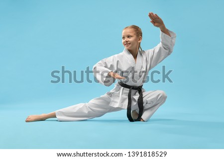 Cheerful little sports woman sitting on twine and practising karate on blue isolated background. Active girl wearing white kimono and black belt doing sport in studio. Concept of karate and jujitsu. #1391818529