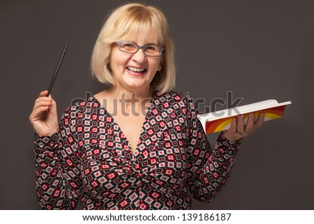 senior woman holding pencil and notebook #139186187