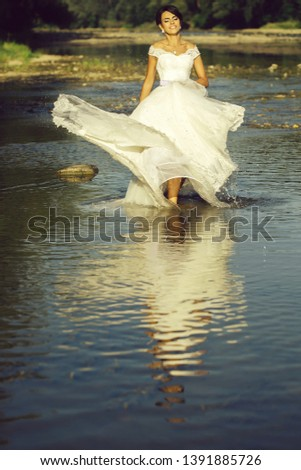 pretty bride pretty woman in long elegant white lace wedding dress stands in lake water sunny day outdoor on natural background #1391885726