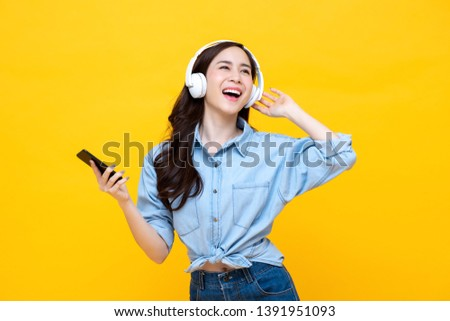 Happy cheerful Asian woman wearing wireless headphones listening to music from smartphone studio shot isolated on yellow background #1391951093