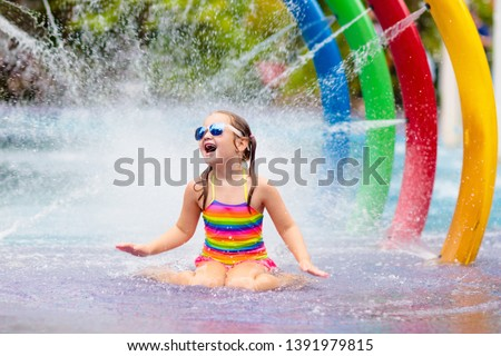 Kids play in aqua park. Children at water playground of tropical amusement park. Little girl at swimming pool. Child playing at water slide on summer vacation in Asia. Swim wear for young kid. #1391979815