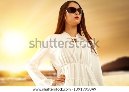 Portrait of a beautiful young brunette. Dark fashionable sunglasses. Beach landscape at sunset. Solar flares of light. #1391995049